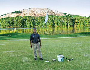 Stone Mountain GC employee Gibbs Valcin stands next to the first 8-inch cup cut at the course, immediately after aerification.