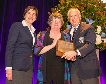 Dr. Patricia J. Vittum, center, is presented with the Green Section award by Kimberly Erusha, USGA Managing Director, Green Section and William L. Katz. (Copyright USGA/Chris Keane)