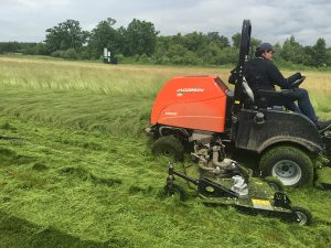 Reineking hops onto a mower himself to take down some of the fine fescue.