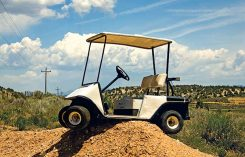 Golf cart stuck on top of dirt mound