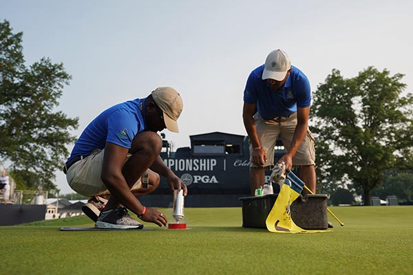 Grounds crew painting the cup on the 18th green during the final round of the 100th PGA Championship held at Bellerive Golf Club on August 12, 2018 in St. Louis, Missouri. (Photo: Montana Pritchard/PGA of America)