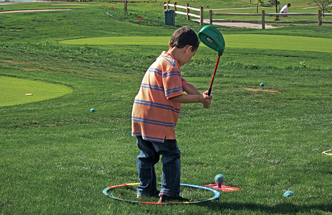 Child teeing off on mini course (Photo: Cattail Creek Mini Course)
