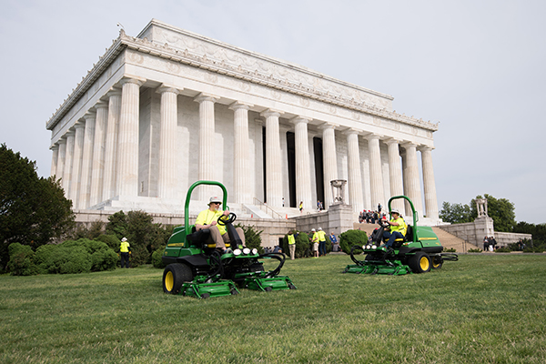 Volunteers mowing near the Lincoln Memorial. (Photo: Kevin Dietsch)