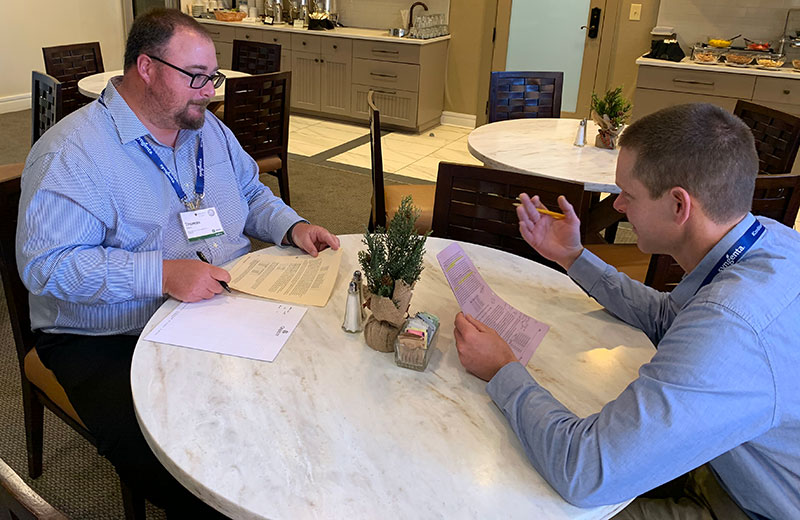 Thomas Slevin (left) and Dave Marach represent a buyer and a seller as they work to negotiate a mock deal at the Syngenta Business Institute. (Photo: Golfdom Staff)