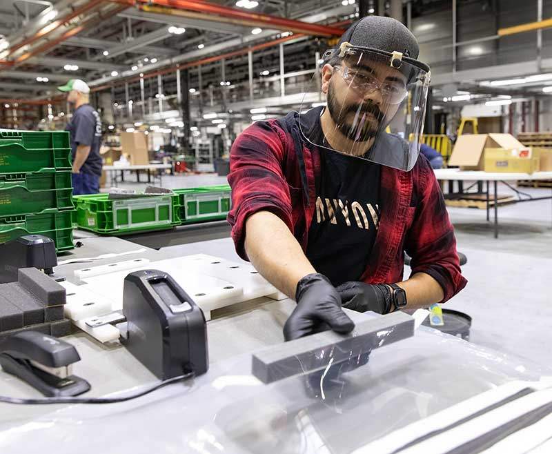 Jose Martinez, an assembler at John Deere Seeding Moline, assembles protective face shields for health care workers. (Photo: John Deere)