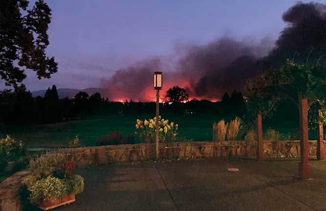A wildfire blazes in the distance as seen from Rogue Valley Country Club, Medford, Ore. (Photo: Craig Hilty)