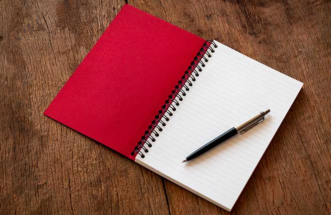 Pen and red notebook (Photo: NooMUboN / iStock / Getty Images Plus/ Getty Images)