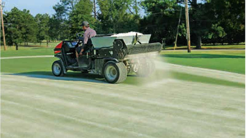 A drop-style topdresser can deliver sand to the putting surface with high precision. This operator is applying 1 cubic foot of sand per 1,000 square feet. (photo by: Brian Whitlark, USGA Green Section)